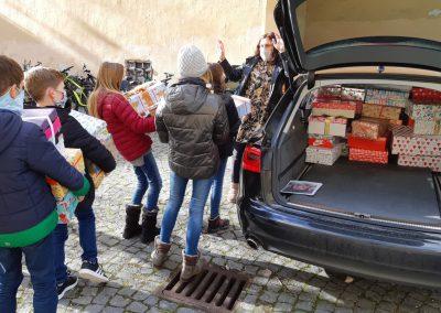 """2020-Weihnachten im Schuhkarton""""Pack eine Schuhschachtel voller kleiner Überraschungen für Kinder in Rumänien! Mach mit! Schenke Weihnachtsfreude!"""", lautete der Aufruf auf den Flyern unserer diesjährigen Weihnachtsaktion. Viele Schülerinnen und Schüler fühlten sich angesprochen und halfen mit, manche sogar mehrfach. So konnten unseren Sekretärinnen innerhalb von knapp drei Wochen eine dicke Wand von Schuhkartons stapeln – 114 an der Zahl! Am 20. November holte unsere Kooperationspartnerin von der Freiraum-Kirche Burghausen die Päckchen ab, um sie auf die Reise in besonders arme Gebiete Rumäniens zu schicken. Für manche Kinder dort ist ein solcher Schuhkarton das einzige Geschenk, das sie an Weihnachten erhalten – dies löste durchaus mitfühlendes Staunen in unseren Klassen aus. Nach dem Verladen der Päckchen in ein geräumiges Auto äußerten sich Kinder der 6b in einem Brainstorming: - """"Ich finde es toll, dass so viele Schüler mitgeholfen haben, die Päckchen zu packen. Ich hoffe, dass die Kinder in Rumänien sich sehr darüber freuen. Ich wünsche ihnen, dass sie in Zukunft sich etwas besser fühlen und wissen, dass wir, die mehr als sie besitzen, für sie da sind, denn: Wenn viele Menschen viele kleine Dinge tun, ist es insgesamt etwas Großes!"""" - """"Es ist so toll, dass so viele Geschenke zusammengekommen sind! Ich liebe es, anderen etwas zu schenken, weil es einen selbst auch glücklich macht. Es hat mir sehr viel Spaß gemacht, ein Geschenk zu packen, weil ich die ganze Zeit daran gedacht habe, wie sich die Kinder in Rumänien darüber freuen werden."""" - """"Es macht mir Spaß, anderen, ärmeren Kindern Freude zu bereiten. Überhaupt anderen Leuten etwas zu schenken bereitet mir persönlich eine noch größere Freude als beschenkt zu werden. Einfach die Freude in den Gesichtern anderer zu sehen und daran zu denken, dass man selbst dies verursacht hat. Auch wenn man nicht anwesend ist, mit etwas Glück sehe ich vielleicht ein Foto davon."""" - """"Wir, die Klasse 6b, durften nicht nur ein Paket"""